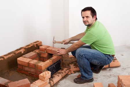 Worker building a danish mass stove from red bricks Stock Photo - 16350725
