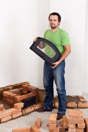 Building a traditional stove for heating - worker at construction site Stock Photo - 16350711