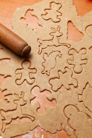 Gingerbread cookie dough cut to christmas themed shapes photo