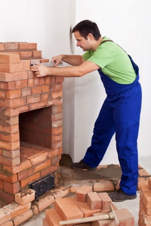 fireclay: Worker building brick stove or fireplace checking it with spirit level