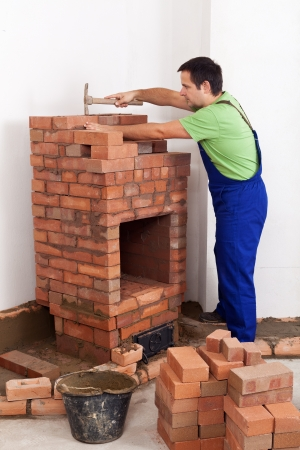 firebox: Worker building a brick stove arranging the building blocks of the firebox Stock Photo