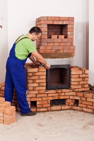 firebox: Worker mounting door to a masonry heater - half finished Stock Photo