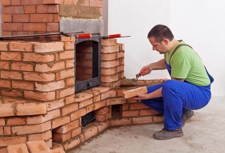 Worker gebouw tegelkachel - het beëindigen van de zithoek Stockfoto