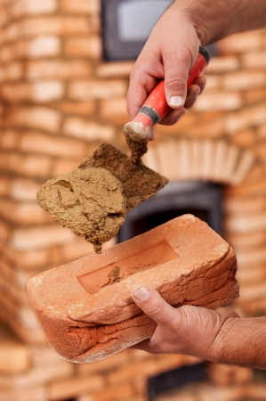 fireclay: Building a masonry heater - closeup on worker hands holding trowel and brick Stock Photo