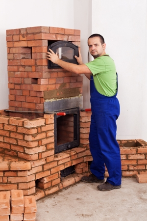 Worker building a masonry heater - trying on the glass door Stock Photo - 16523258