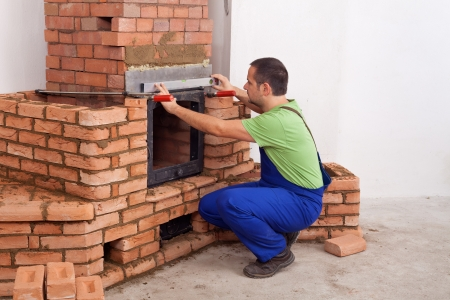 firebox: Worker building a masonry heater in a new home - copy space