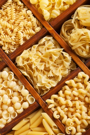 raw gold: Pasta mix in compartmented wooden box - closeup