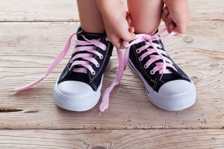 Child hands tie up shoe laces on old wooden floor background Stock Photo