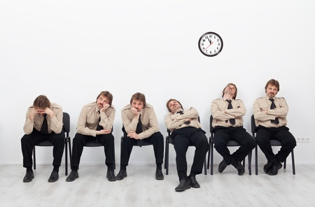 Bored, stressed and exhausted people sitting on chairs waiting