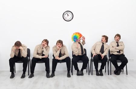 Stressed mensen die wachten op een sollicitatiegesprek - met een clown bijhouden van de goede geest Stockfoto