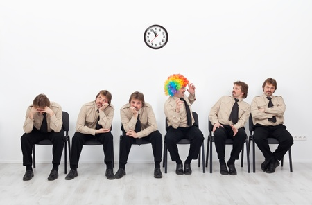Stressed people waiting for a job interview - with a clown keeping up the good spirit