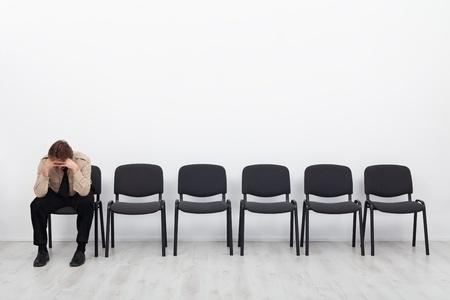Eenzaam en wanhopig zakenman zittend op een stoel - stress begrip