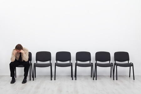 Lonely and desperate businessman sitting on a chair - stress concept