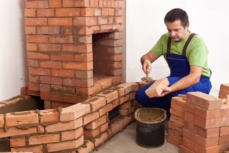 Construction of a masonry heater - worker building the firebox and the flue area photo