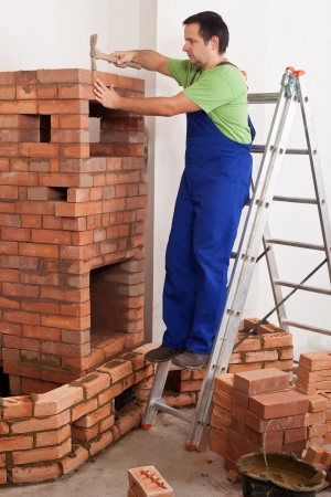 Worker building masonry heater - finishing the firebox with chamotte bricks Stock Photo - 16585085