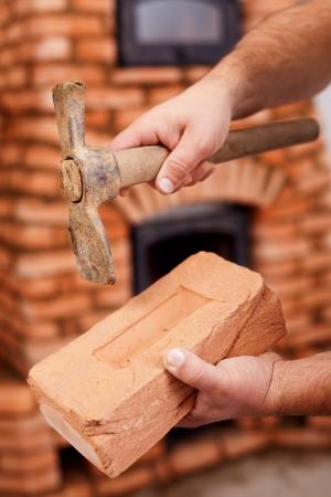 Mason hands with brick and hammer - masonry heater in background photo