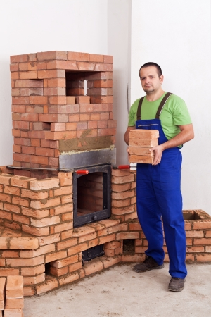 fireclay: Professional worker building masonry heater - carrying bricks