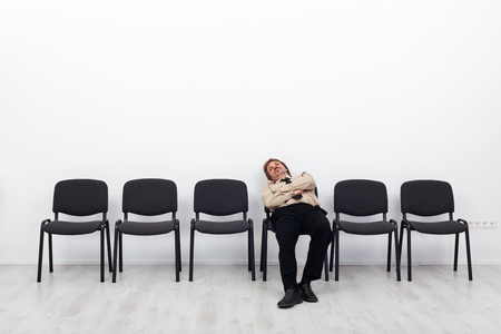 Tired businessman waiting - sitting on a chairs row Stock Photo