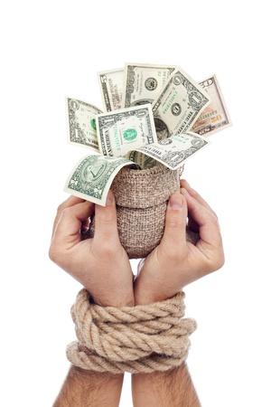 enslave: Prisoner of profit - man holding bag of money with hands tied up Stock Photo