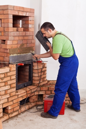 Worker installing door to a masonry heater - working with welding machine photo
