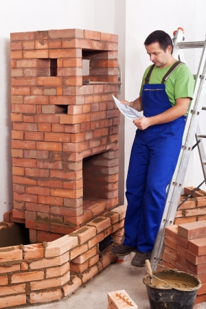 firebox: Worker building masonry heater - consulting the plan standing on a ladder