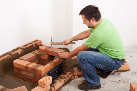 Man building masonry heater or fireplace - fitting the next brick Stock Photo - 17452643