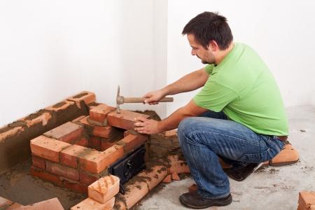 Man building masonry heater or fireplace - fitting the next brick Stock Photo - 17452643