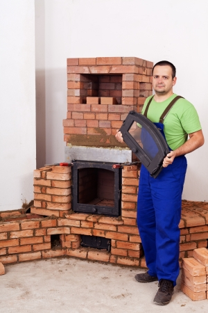 Mason building fireplace - fitting the doors to the firebox Stock Photo - 17499804