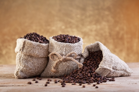 Roasted coffee beans in burlap bags on old table Stock Photo - 17536694