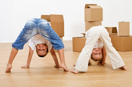 Kids playing in their new home having fun in front of cardboard boxes photo