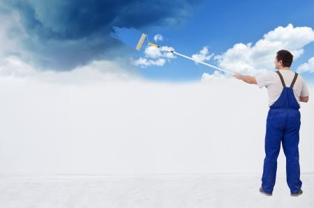 Worker schilderen van de muur van stormachtige hemel naar pluizige wolken - met een kopie ruimte