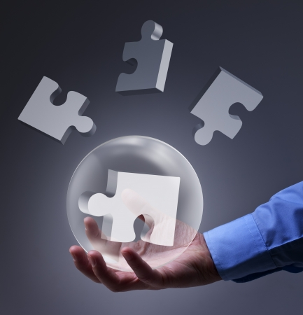 Male hand holding glass sphere with puzzle pieces - solution concept Stock Photo - 17931666