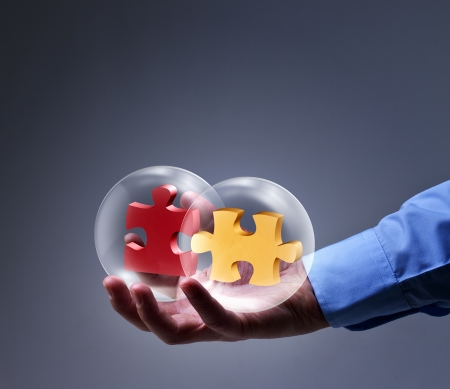 two piece: Businessman presenting a brand new solution - two puzzle pieces in glass spheres Stock Photo