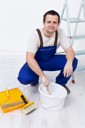 repaint: Worker preparing the paint and utensils to repaint a room Stock Photo