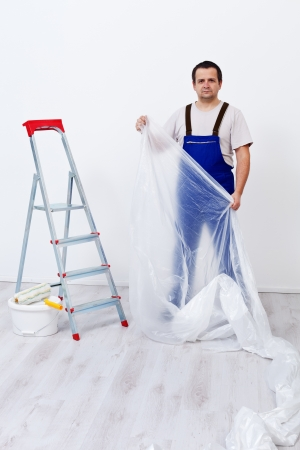 foil roll: Worker laying protection film before painting indoors Stock Photo
