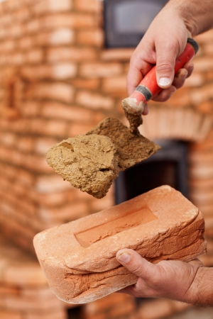 Masonry heater builder hand with brick, trowel and clay mortar Stock Photo - 17931697
