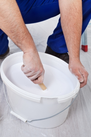 thinning: Worker thinning the paint - stirring it with wooden stick, closeup Stock Photo