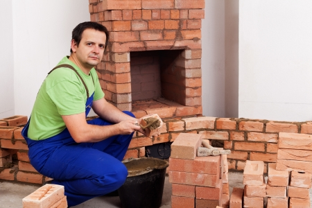 Masonry worker building rustic traditional fireplace photo