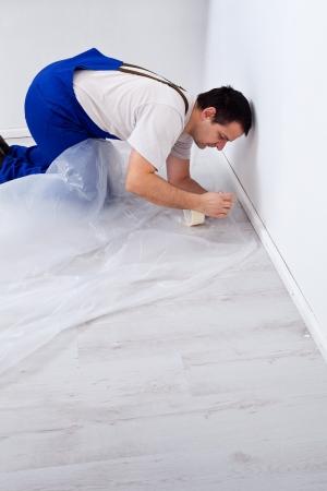 Worker leggen beschermende folie voor het schilderen - geknield op de vloer Stockfoto