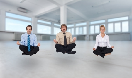 Startup business - young business people meditating in empty office space photo