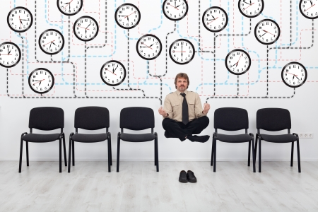 Expert time management - businessman controlling lots of wall clocks photo