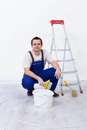 repaint: Worker with paint, brush and ladder preparing to repaint the wall