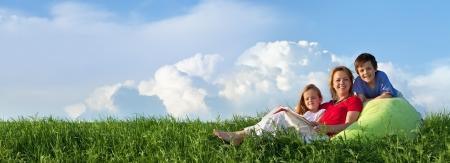 Familia de relax al aire libre en la hierba fresca primavera - panorama