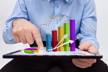 document management: Zakenman het wijzigen van de jaarverslag grafieken - werken aan een tablet-computer Stockfoto
