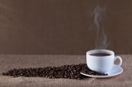 steaming coffee: Cup of fresh and hot steaming coffee on burlap surface