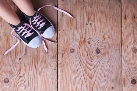 lacing sneakers: Child feet in sneakers on old wooden floor - with copy space Stock Photo