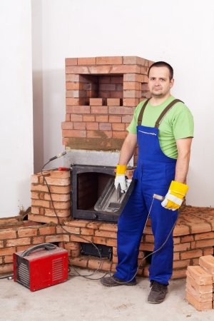 Worker mounting the door of a brick masonry heater with a welding equipment photo