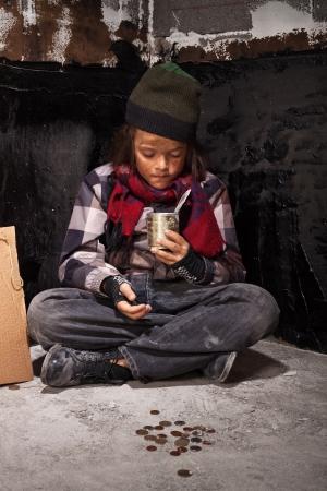 Bedelaar kind jongen beoordelingen door het geld dat hij ontving op zoek naar blikje Stockfoto