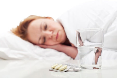 Woman fighting sickness with pills and resting - focus on medication photo