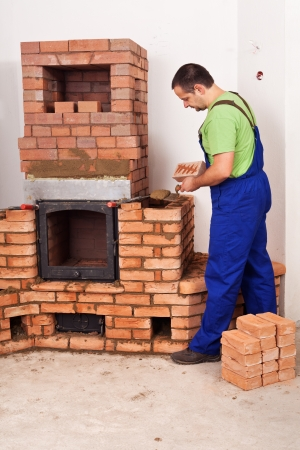 Mason building a masonry heater from red bricks and clay mortar photo